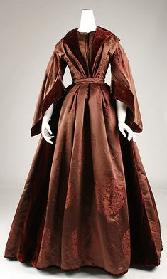 Dress, circa 1850, British, silk brocade. Classic round Chinese duelling dragons pattern. Deep red velvet collar, cuffs, and trim. Looks like a warm winter outfit. In storage at the Met.