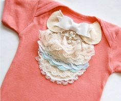 Layered lace trim ,bib front panel with peter pan collar.  Lovely, shabby chic onesie for a baby girl.  Ribbon, lace & pearl buttons adorn this lovely gift for any girly girl.
