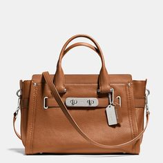 """Statement belting with double-turnlock hardware updates one of our most popular designs with a little bit of """"swagger."""" Named for a bold, brass-trimmed Bonnie Cashin design from 1967, this very modern carryall has a thoroughly organized interior and a detachable strap for shoulder or crossbody wear."""