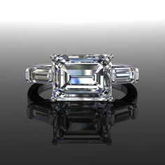 A diamond and Moissanite east west engagement ring in 14 kt White Gold featuring a 2.50 ct emerald cut Forever Brilliant Moissanite by Charles