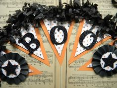 "This banner is made from an orange heavy paper and a sweet halloweenish polka dot paper. ""Boo"" is spelled out and hand glittered. Paper medallions are on both ends of the banner with a black glittered star on top. Black tissue fringe lends a festive touch to this banner with black seam binding ribbon stringing it all together.   The banner is appx. 27"" long and each tag is appx. 5"" x 4""."
