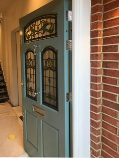 This Edwardian style front door is beautifully framed by amazing brick arch. The flowers on stained glass and delicate blue door colour suit perfectly with the whole design of this house. Exterior Doors With Glass, Entry Doors With Glass, Exterior Front Doors, Glass Front Door, Stained Front Door, Stained Glass Door, Painted Front Doors, Modern Front Door, House Front Door