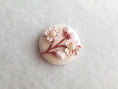 桜の花と蕾のブローチ満開まで もう少し、あと少し、、この木の下を通るたびに思うそれが私の春の楽しみ≪作品について≫直径約2.5cmのくるみボタンにつまみ細工の桜と蕾をあしらいました。満開の桜とはまた違った控えめな美しさをお楽しみください。≪サイズ≫くるみ...