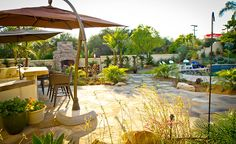 The back yard of this landscape design project encompasses a living room, dining and kitchen area, as well as a large swimming pool and deck.https://ecomindedsolutions.com/project/front-and-backyard-poway-ca/
