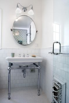 This contemporary guest bathroom features white tile wainscoting along the walls and a penny tile floor. Polished metal legs support the simple white sink under an oval mirror and wall-mounted light fixture.