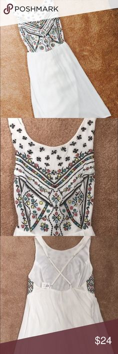 Sundress Cute white sundress with colorful embroidery across the chest. Adjustable back straps that come together in a criss cross. Never worn. Love Stitch Dresses Backless