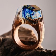 The jeweler Secret Wood (previously) has been producing even more miniature cities and landscapes, each ethereal universe living inside a resin geometric dome on top of their handmade wooden rings. In