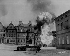 Soldats du 101e régiment d'infanterie US passent devant une remorque de fuel qui brûle sur la place de Kronach à Bayreuth en Allemagne, le 14 avril 1945.