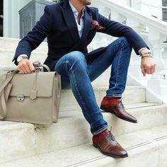 Shop this look on Lookastic: https://lookastic.com/men/looks/blazer-dress-shirt-skinny-jeans/18983 — Light Blue Dress Shirt — Burgundy Polka Dot Pocket Square — Black Leather Watch — Beige Leather Briefcase — Blue Skinny Jeans — White Bracelet — Red Socks — Brown Leather Oxford Shoes — Navy Blazer