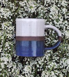This handmade ceramic coffee mug is ready for business. And by business, we mean coffee. Or tea, if that's your thing. Each clay mug is carefully crafted by hand and then glazed in blue and cream.