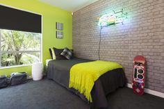 The final reveal! A zingy lime green wall teamed with cool exposed brick wallpaper and charcoal carpet for this teenage boys bedroom. Decorating products are available in New Zealand through Guthrie Bowron stores.