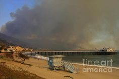 Fine Art Photography by Nina Prommer - The fire is seen behind the pier in Malibu, California October 21, 2007. Firefighters watch the brush below. The wildfire fanned by powerful winds burned out of control on Sunday in the celebrity seaside enclave of Malibu, forcing hundreds of people to flee and destroying a handful of multimillion-dollar homes.