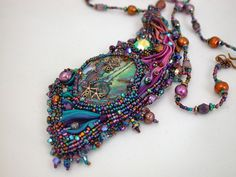'The Long Slow Telling of her Tale' bead embroidery, mixed media art jewelry. See my Facebook page, Handcrafted Beaded Art and Jewelry by Regina Roper, for a full description and more photos.