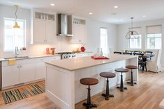Transitional kitchen features a white center island topped with light grey quartz lined with backless industrial wood and iron swivel counter stools.
