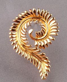 18kt Gold Clip/Brooch, Tiffany & Co., Schlumberger, designed as a curling naturalistic frond, 9.3 dwt, lg. 1 3/4 in., signed.