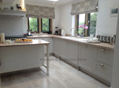 Painted shaker style kitchen with a modern country feel. In Farrow & Ball Cornforth White. From Kitchen & Bedroom Store.