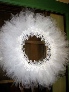Snowflake Christmas Wreath: I took a metal clothes hanger and stretched it into a circle. Then I tied the tulle to the hanger until it was completely covered (took 6 yards of tulle). Then with a hot glue gun, I glued the plastic glitter snowflake ornaments around the center of the wreath. I bet this would be so cute in Christmas colors.