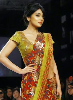 The modern woman WALKS TALL  Shriya Saran, looks the picture of confidence as she walks the ramp wearing a printed Lime green and red coloured georgette saree embellished with gota work, at the winter Lakme Fashion Week.