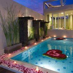 Pink roses petals around pool area with large heart in petals inside! Romantic!