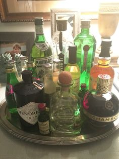 In my staging projects I love using bar cart vignettes to highlight a fun entertaining area in the home.  This is my bar setup at home, the key to a good bar vignette is first having something to contain it, here I am using an oval silver platter.  Grab varied and interesting bottles, with a mix of colors that balance dark/light/color and a mix of shapes and heights, notice I have round, hexagon, cylinder, skinny, fat.  Play around with it until it feels right, Then make yourself a cocktail!