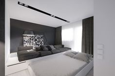 50 Square Meter Space Saving Apartment Layout For Young Family. A large sofa in the living room exists atop a platform, underneath which is hidden a double bed that slides out at night. The living room also includes a workspace, nestled amid the storage areas in the walls.