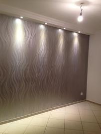 Wandleuchten und farbige Tapete mit feinen Linien tragen zur modernen Raumgestaltung bei. Tapezierarbeiten von Malerplus Aykut Aslan in Haan (42781) | Maler.org