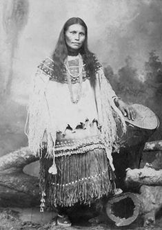 An old photograph of an Apache Woman Wearing Both a Hide Blouse and Skirt.