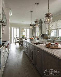 White and gray kitchen features a long gray wash oak center island topped with gray and white marble illuminated by a stainless steel sink and gooseneck faucet illuminated by industrial cage lanterns.
