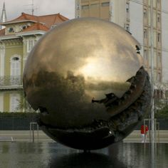 Italian artist Arnaldo Pomodoro has left his golden sphere monuments all over the world. One of them has become the symbol of Pesaro in Le Marche. Monuments, Italian Artist, Holiday Destinations, All Over The World, Europe, Travel Tips, Explore, Notes, Contemporary Sculpture