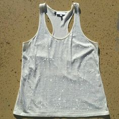 """NWOT JL Racerback Tank Top New without tags, creme colored tank top with silver rhinestones. Brand: Jennifer Lopez. Size: Large. When laying flat, length 27"""", across the chest 19"""". 60% Cotton, 40% Modal. All rhinestones in tact. No rips, tears, flaws, or defects. Comes from a smoke free home. No trades or holds, thank you. Jennifer Lopez Tops Tank Tops"""