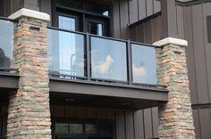 Glass railing balcony with stone pillars