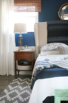 Master Bedroom Makeover // grey rug, navy walls, white curtains, white bedding, upholstered headboard, wood floors, small night stand, gold lamp, bamboo shades // Light & Bright Eclectic Home Tour by @CraftivityD