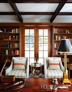 Home library with warm wood bookcases flanking French doors, pair of charming chairs and lamps