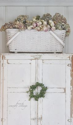 Beautiful armoire with basket of flowers on the top.