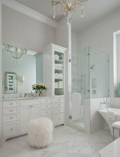 White and gray master bathroom features walls painted soft, creamy gray lined with white vanity cabinets topped with white marble under a frameless mirror situated next to a tall mirrored linen cabinet.