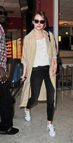 Emma Stone wears a white henley, khaki trench coat, skinny jeans, and Adidas sneakers