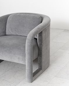 A pair of elegantly curved club chairs designed by Milo Baughman; each chair features a removable back cushion for extra support. The chairs have been newly upholstered in a beautiful ash grey vel…