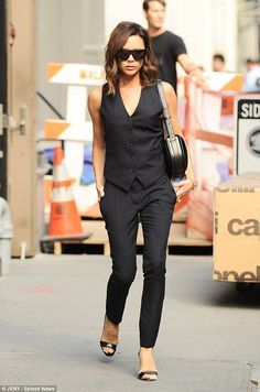 Sophisticated: Victoria Beckham, 42, showed everyone who's boss as she left a photoshoot in New York City on Friday in a chic navy pinstripe suit