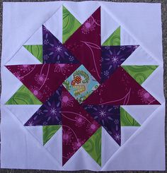 Star Block for Amanda. For Twelve Month Quilting Bee.  I added the green leaves and the fushia dandelions from my stash.  Seriously love this block. Tons of half-square triangles, and a partial seam too, but the outcome is totally worth it.  A huge THANK YOU to Lainey for the awesome tutorial: laineybugdesigns.blogspot.com/2011/08/modern-star-block-t...