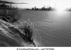 Winter sunrise over the icy river. The sun rises over the icy river at the rural finland. the sunlight colors the frosty scenery amber. River Bank, Royalty Free Photos, Finland, Mists, Netherlands, Greece, Sunrise, Spain, Poster Prints