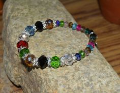 """Beautiful, multi color bracelet made with larger, (10 mm) crystals and small, (4 mm) beads with a Faith charm. This bracelet reminds you of your faith- in God, the angels, in humanity and in yourself.  """"Faith is taking the first step even when you don't see the whole staircase.""""- Martin Luther King, Jr."""