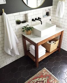 Simple bathroom vanity. Wood, marble and black tile floors. More