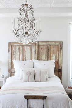 Distressed barn door headboard + Chandelier + crisp white linens = Beautiful!!
