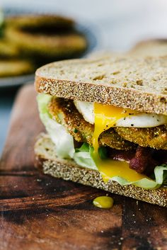 A delicious fried green tomato BLT sandwich with a runny fried egg. This image is exclusively licensable as a royalty-free stock photo through Stocksy United. #StockPhoto #FoodPhotography #FoodStillLife
