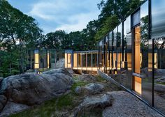 This home nestles into a rocky outcrop in New York State, with mirrored cladding that reflects the forested landscape and sky