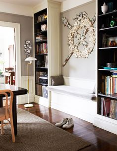Built-in bench and bookshelves in home office with serious art piece above