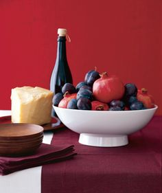 "Adding a white bowl to my list of ""needs"" Natural Pairing  Add jewel-toned fruit to a white bowl with sensuous lines for an easy arrangement. Look for fruits of differing sizes and shapes but with similar coloring, as with these plums and pomegranates."