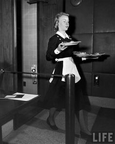 Waitress carrying trays and plates of food at Schrafft's in Rockefeller Center. New York, August 1948. Photographer: Cornell Capa.