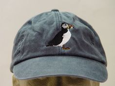 NEW EMBROIDERED PUFFIN BIRD WILDLIFE HAT (HATS PICTURED ARE NAVY BLUE AND BURGUNDY) Adams Optimum 6 Panel Baseball Hat Low Profile – 100% Cotton Twill Adult Cap Pigment Dyed – Garment Washed Hat 6 Panels with Sewn Matching Eyelet Visor with 3 Rows of Stitching Pre-formed Bill - Leather Strap with Brass Grommet Adjustable – One Size Fits Most An Extremely Comfortable Baseball Hat! Enjoy the Embroidered Puffin Bird Wildlife Hat! We have 24 Different Solid Color Baseball Hats Available...
