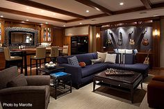 Wonderful basement remodel with a full bar, sectional couch, hanging guitars and hardwood floors. Click on the image to see other great man cave ideas. #basement #mancave